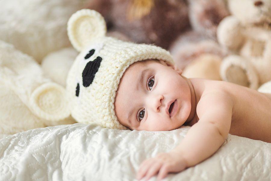 Schattige baby van 25 weken oud met dierenmuts op