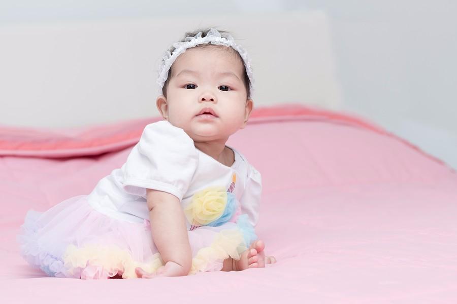Aziatische baby van 26 weken oud zit en leunt op haar armpje