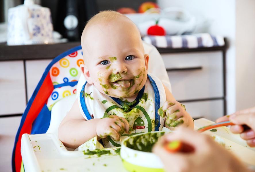 Baby eet groente en fruit en zit helemaal ondergesmeerd
