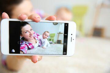 Moeder maakt foto van haarzelf en haar kindje met smartphone, socialmediagebruik