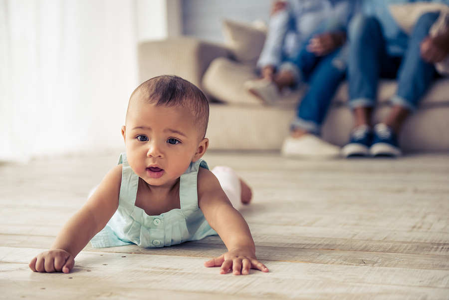 Een kindje met een lui oog ligt op haar buik