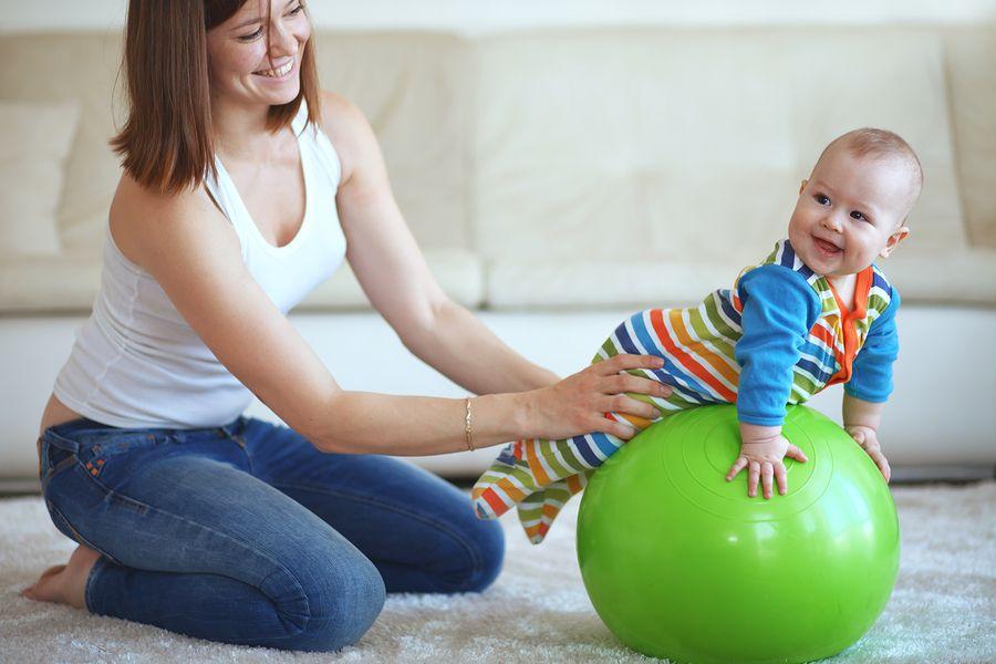 Lachende baby van 6 maanden oud ligt op fitness bal, moeder houdt hem bij zijn heupjes vast