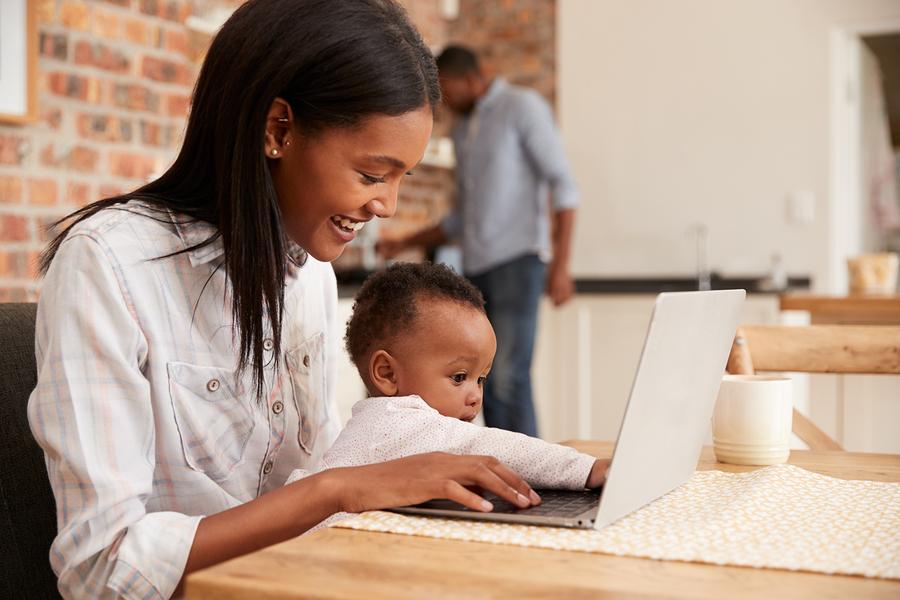 Moeder en baby achter laptop om ouderschapsverlof te regelen
