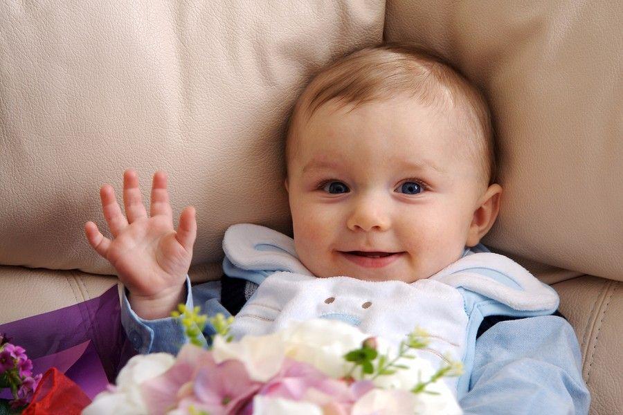 Baby van 7 maanden oud lacht en zwaait
