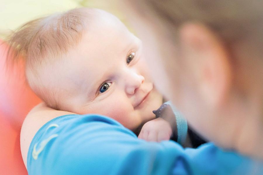 Baby kijkt pedagogisch medewerker liefdevol aan