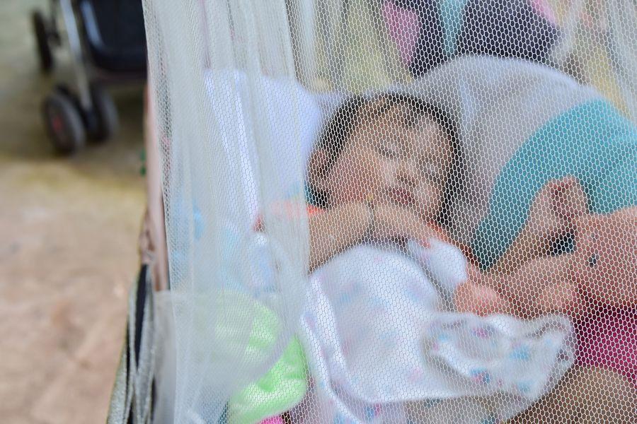 baby slaapt buiten onder muskietennetje tegen insecten