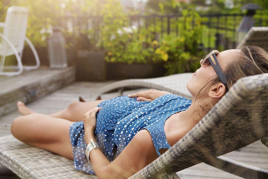 zomer zwanger: een zwangere vrouw ligt in de zomer op een ligbed