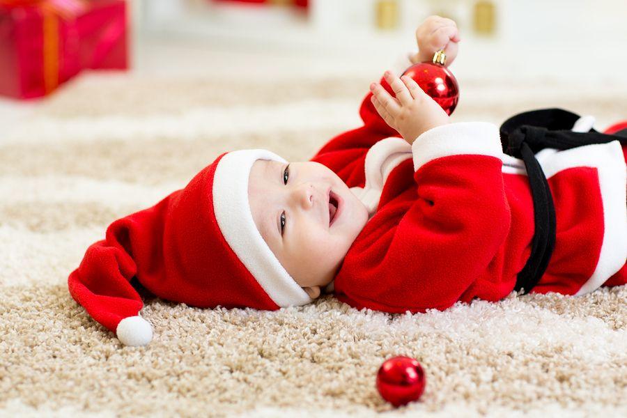 Baby ligt in kerstpakje op kleed met een kerstbal in zijn handjes