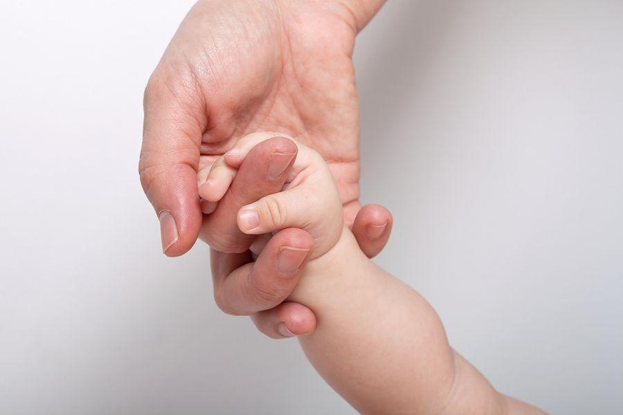 Moeder houdt handje vast van baby die anders is
