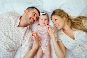 Ouders en baby met goede hechting liggen op bed gelukkig te zijn met elkaar