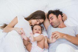 Gelukkig stel ligt met hun baby op bed te knuffelen