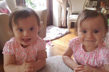 Tweeling meisjes met roze jurkjes