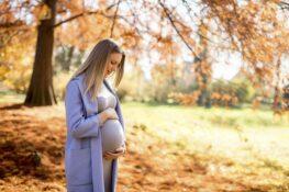 vrouw die zwanger is staat in het bos