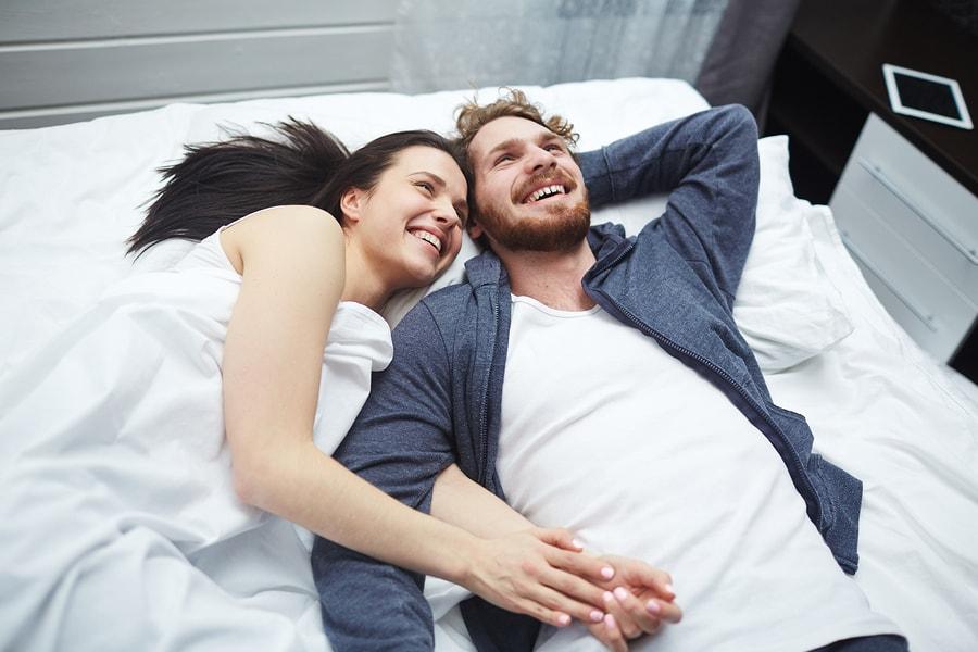 jonge vrouw van 0 weken zwanger en man liggen samen op bed