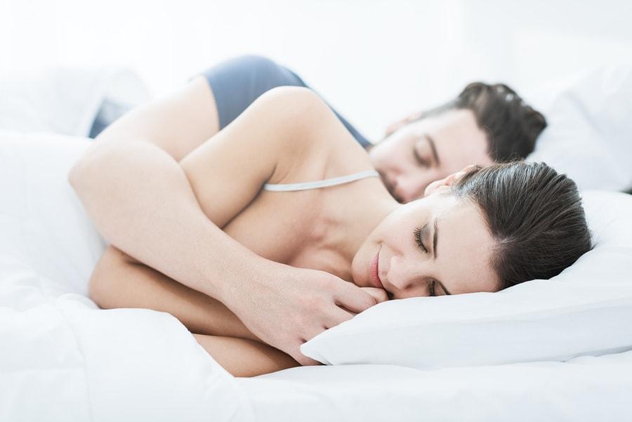 Vrouw van 9 weken zwanger ligt samen met partner op bed van ze is vermoeid door zwangerschap