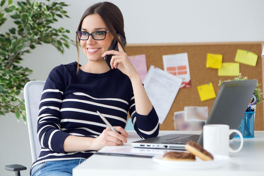 Vrouw zit op kantoor langend aan de telefoon achter laptop na haar zwangerschapsverlof