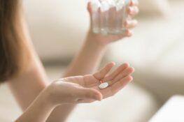 Vrouw heeft witte foliumzuur pil in haar hand en glas water