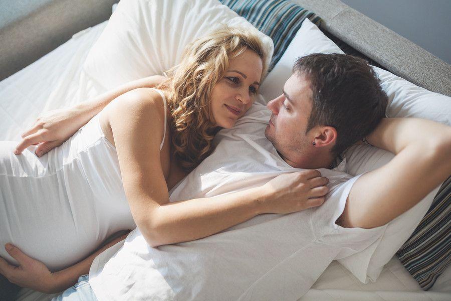 Vrouw van 20 weken zwanger en man liggen liefdevol op bed