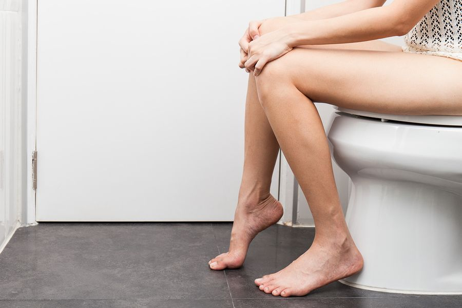 Zwangere vrouw met blaasontsteking zit op het toilet