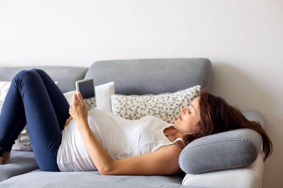 Vrouw van 27 weken zwanger bekijkt geboortekaartjes