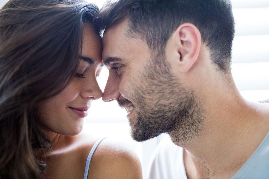 Man kijkt vrouw die 42 weken zwanger is liefdevol aan
