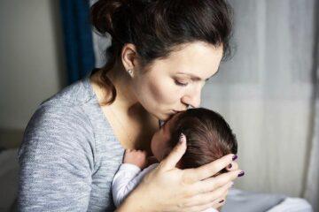 Baby heeft last van regeldagen en moeder kust baby liefdevol op hoofdje om hem te troosten