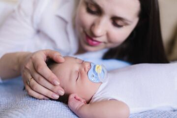 Moeder kijkt liefdevol naar slapend baby'tje met zeldzame ziekte