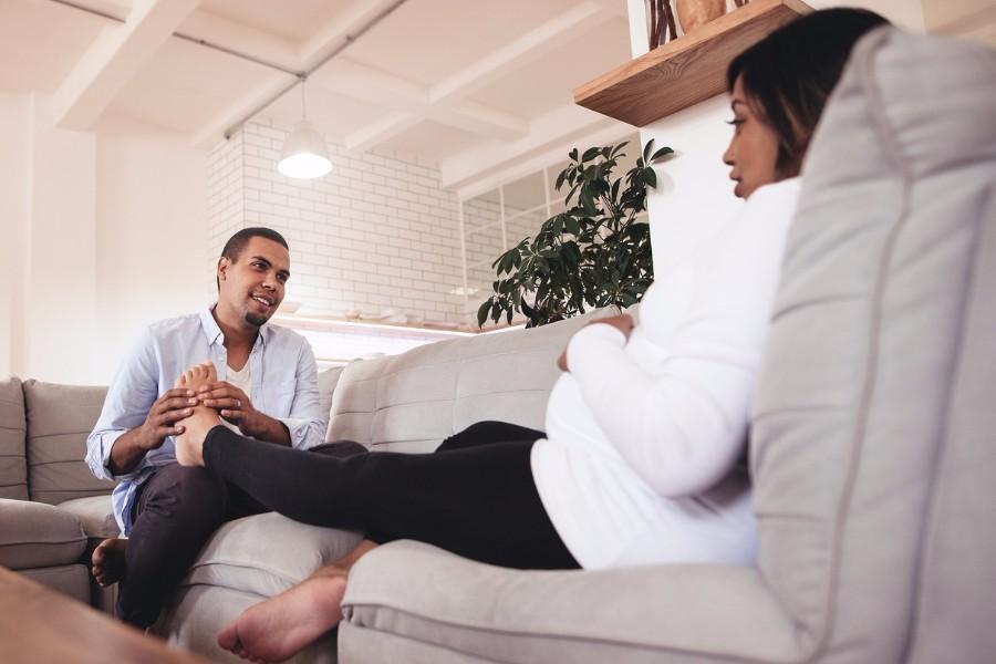Zwangere vrouw heeft kramp in haar kuit en man masseert haar voeten