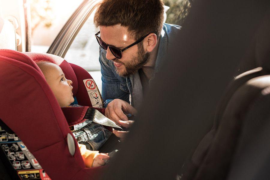 autoverzekering en baby, vader bevestigd baby veilig in autostoeltje