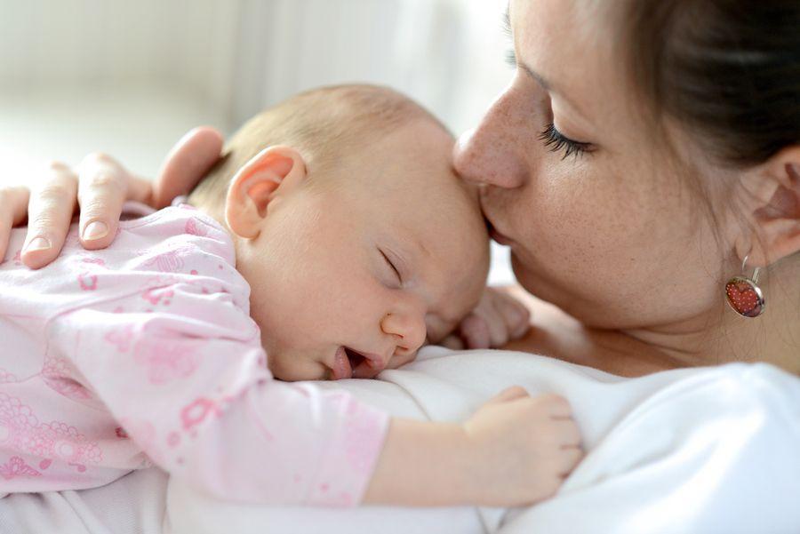 Moeder heeft baby op borst liggen, veilig beschermd tegen kinkhoest