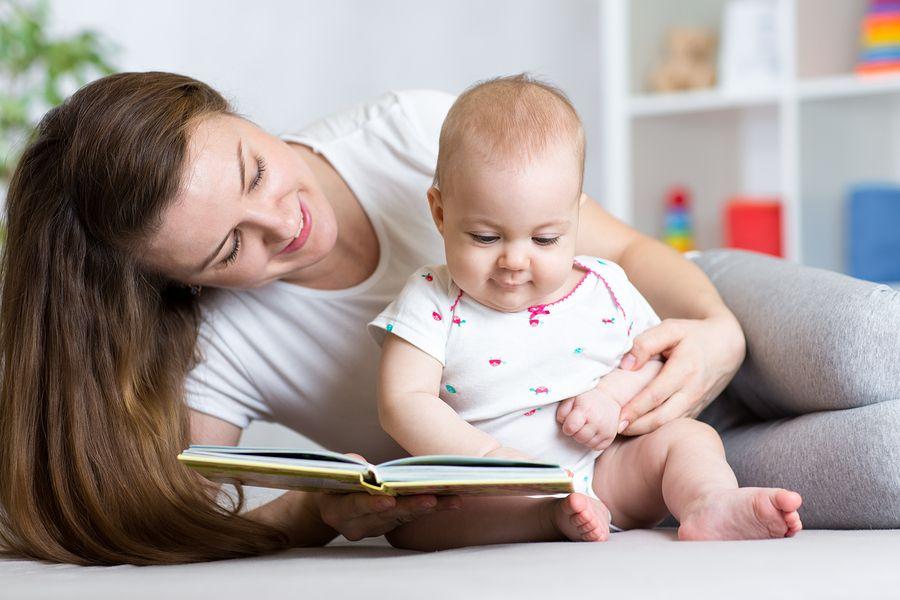 moeder leest haar baby een verhaaltje voor om zijn taalontwikkeling te stimuleren