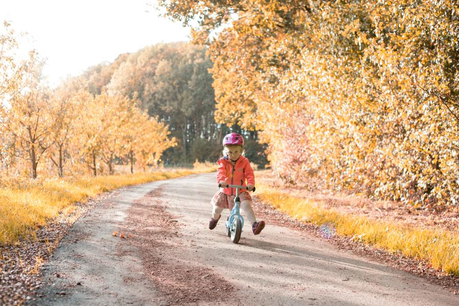 Kindje speelt met loopfiets op bospad