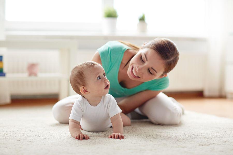 Moeder gaat samen met baby van 9 maanden oud kruipend door huis voor veiligheid