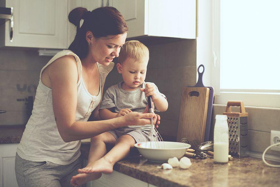 Baby van 17 maanden oud helpt zijn moeder in de keuken