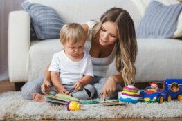 Moeder en zoontje spelen met babyspullen op het kleed