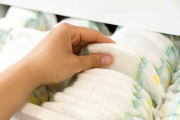 Iemand die de juiste pampers luier voor zijn baby uit een lade haalt