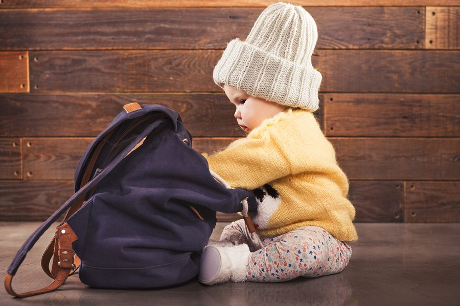 Baby van 14 maanden oud kijkt nieuwsgierig in tas