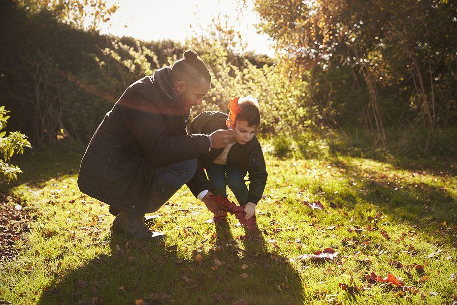 Vader en baby van 22 maanden oud zoeken bladeren in het bos