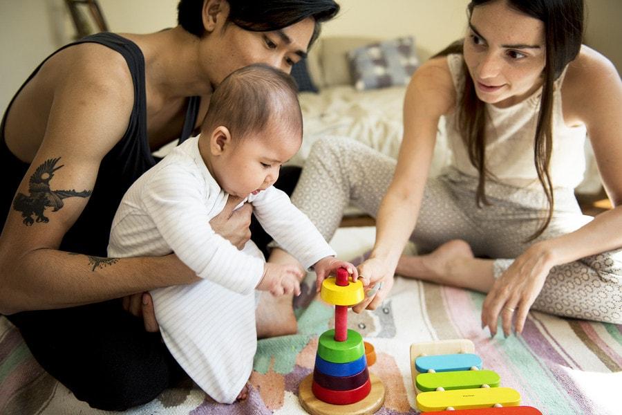 Baby van 23 weken oud speelt samen met vader en moeder met een stapeltoren