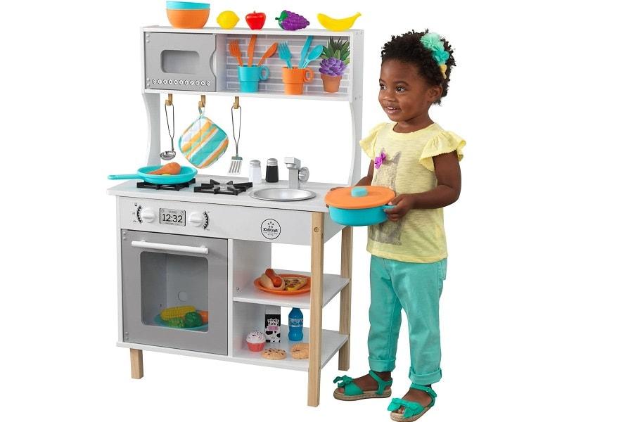 Baby van 24 maanden oud speelt in een speelgoed keukentje