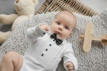 Baby draagt als kerstkleding een overhemdromper en strikje