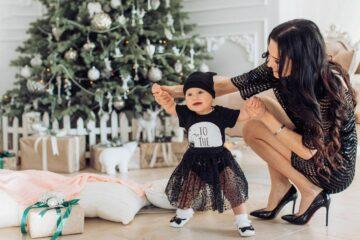 Baby draagt als kerstkleding een kerstjurkje