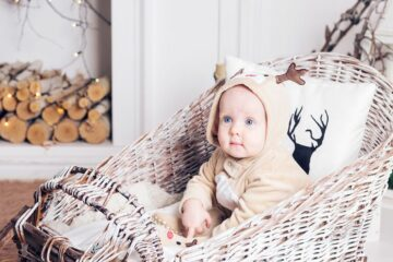 Baby heeft rendierpakje aan als kerstkleding