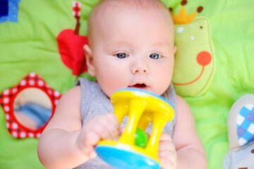 baby ligt op speelkleed met speeltje