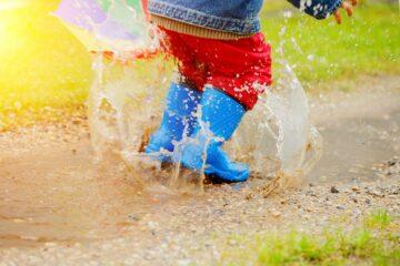 Kindje met blauwe regenlaarsjes springt in regenplas