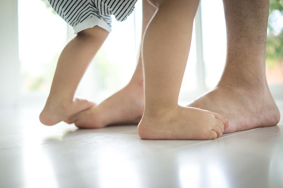 Babyvoetjes op de voeten van zijn moeder