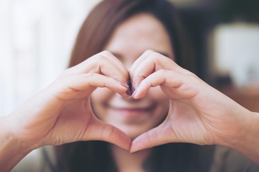 Vrouw vormt een hartje met haar handen