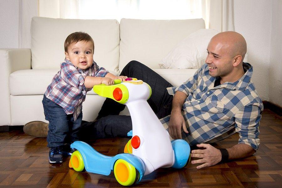 Vader en baby spelen met loopwagen
