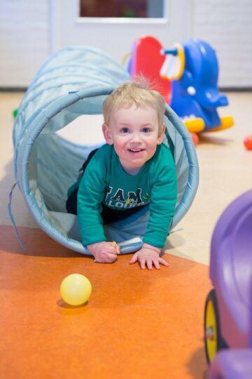 Kindje kruipt door tunnel bij kinderdagverblijf