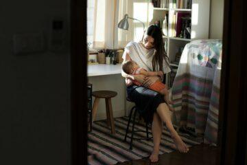 Vrouw geeft borstvoeding en kijkt naar wat ze daarvoor nodig heeft